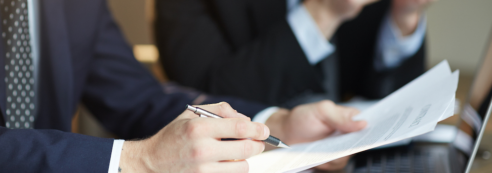 family office reviewing paperwork and signing contract papers at table during meeting